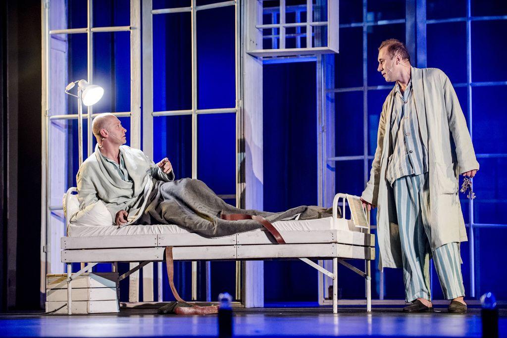 Na szpitalnym, białym łóżku w pozycji półleżącej znajduje się z lewej strony Iwan Bezdomny zwrócony w stronę stojącego przy nogach łóżka Mistrza. Obydwaj mężczyźni są w pasiastych piżamach i jasnych szlafrokach, rozmawiają ze sobą. Mistrz trzyma w lewej dłoni pęk kluczy. Scenografię tworzą duże ramy okienne, wyglądające jakby były zakratowane.