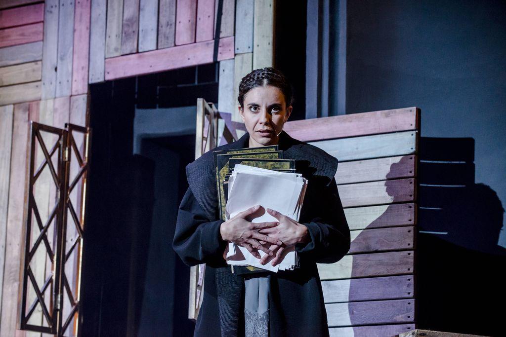 W centralnej części stoi kobieta, ma włosy splecione w okalający głowę warkocz, ubrana jest w ciemnoniebieski płaszcz. Małgorzata patrzy w dal, przyciska do siebie plik kartek i kilka dużych zeszytów. W tle ściana z drewnianych desek, metalowa okiennica.