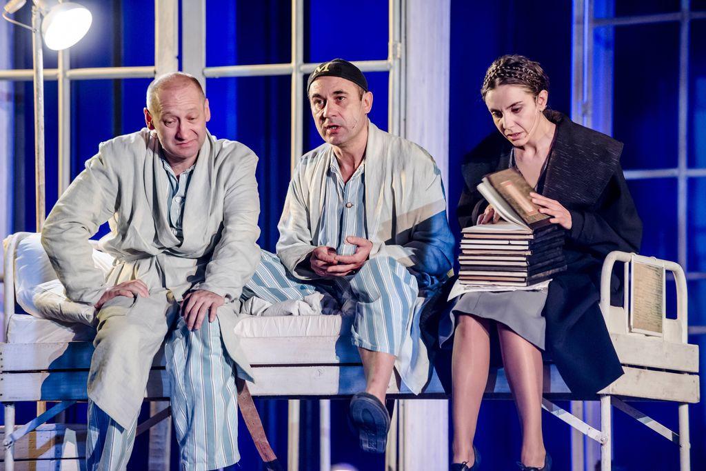 """Na szpitalnym, białym łóżku siedzą trzy osoby. Z lewej Iwan Bezdomny, obok niego Mistrz, a z prawej – Małgorzata. Rozmawiający mężczyźni są ubrani w pasiaste piżamy i jasne szlafroki, Mistrz ma na głowie czarną czapeczkę – myckę, z żółtą literą """"M"""". Małgorzata ma na sobie czarny płaszcz i szarą spódnicę, ciemne włosy ma splecione w warkocze spięte wokół głowy. Na kolanach trzyma stertę dużych zeszytów, jeden otwiera i patrzy w jego kierunku."""