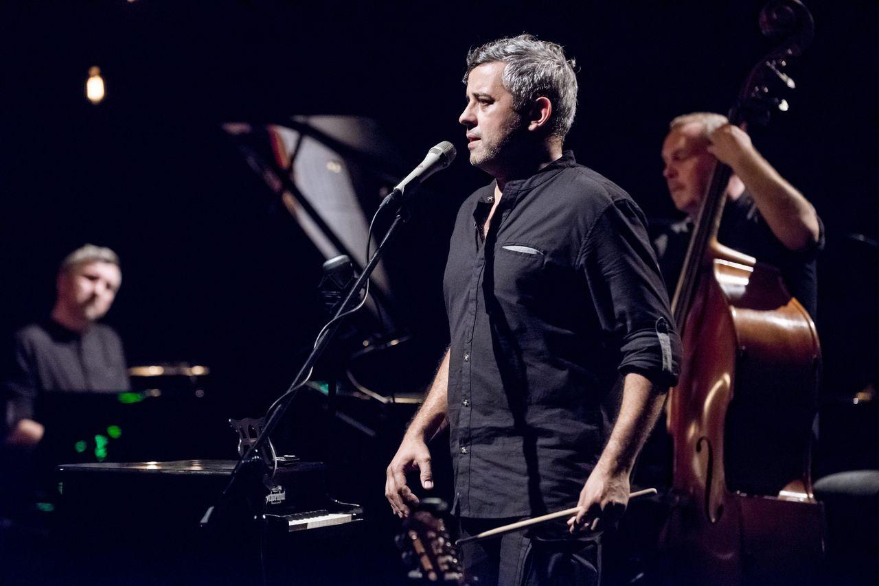 Przed mikrofonem stoi Kondar Imiela, zwrócony do widowni lewym profilem. W ręku trzyma pałeczkę do perkusji. W tle nieostre postaci Piotra Dziubka przy fortepianie i Adama Skrzypka z kontrabasem.