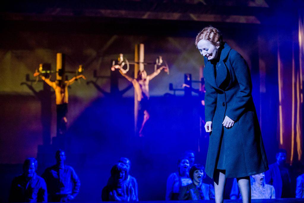 Z prawej strony stoi lekko pochylona, płacząca Kobieta w czarnym płaszczu. W tle widać trzy krzyże z wiszącymi na nich postaciami. Pomiędzy nimi, a Kobietą, znajduje się grupa śpiewających osób.