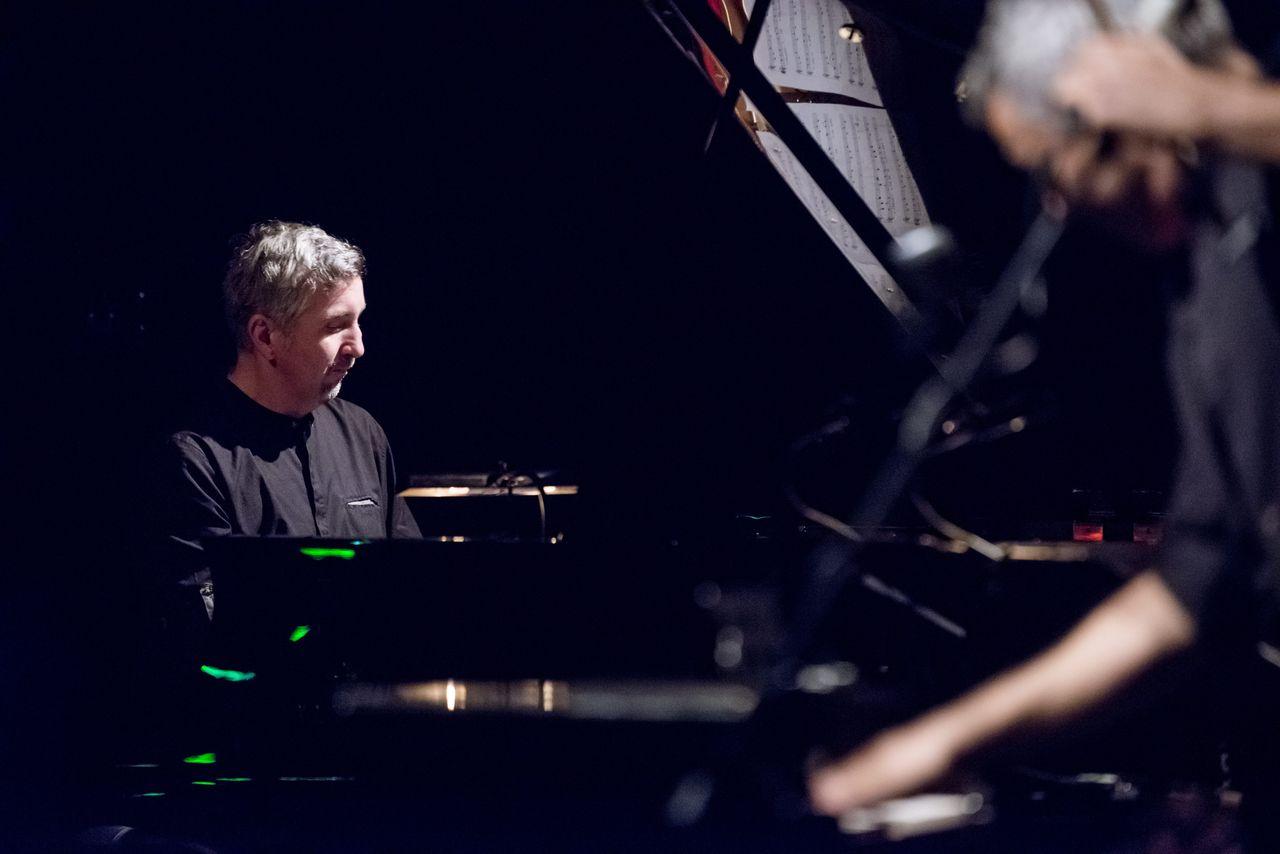 Piotr Dziubek siedzący za fortepianem. Widać go do piersi, ma na sobie czarną koszulę, patrzy na klawiaturę. W otwartej klapie fortepianu od wewnątrz odbijają się nuty. Na pierwszym planie nieostra postać Konrada Imieli.