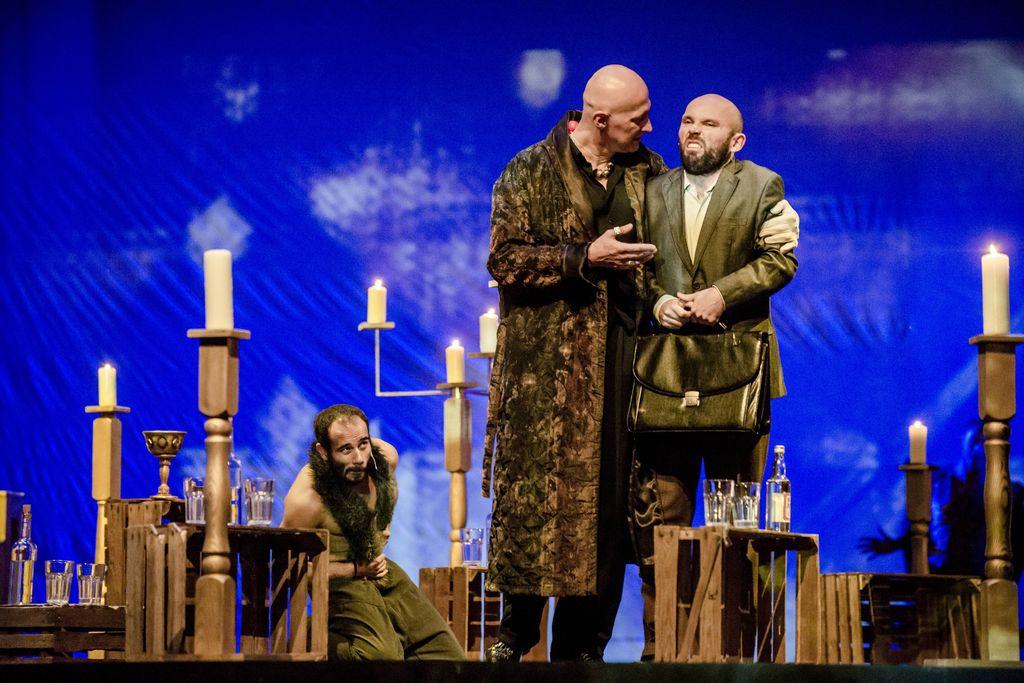 Wśród drewnianych skrzynek, na których i obok których, znajdują się lichtarze i świece, stoi dwóch mężczyzn na pierwszym planie, a jedna postać – Behemot, klęczy z tyłu. Wysoki, łysy Woland w eleganckim, długim, brązowym szlafroku lewą ręką obejmuje człowieka w garniturze i z teczką w dłoniach. Woland coś mówi, głowę ma zwróconą w stronę mężczyzny, kieruje w jego stronę prawą dłoń. Mężczyzna z grymasem na twarzy wygląda na niezadowolonego. Przed nimi, na skrzynce stoi butelka wódki i dwie szklanki.