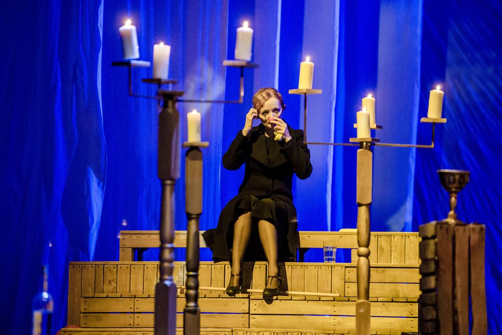 Kobieta siedzi na drewnianym podeście, na niebieskim tle, wśród lichtarzy ze świecami. Ma na sobie czarny płaszcz, rajstopy i ciemne buty. Prawą dłonią dotyka spiętych, rudych włosów, drugą dłoń podnosi ku ustom. Ma rozmazany – jakby od łez, makijaż oczu.