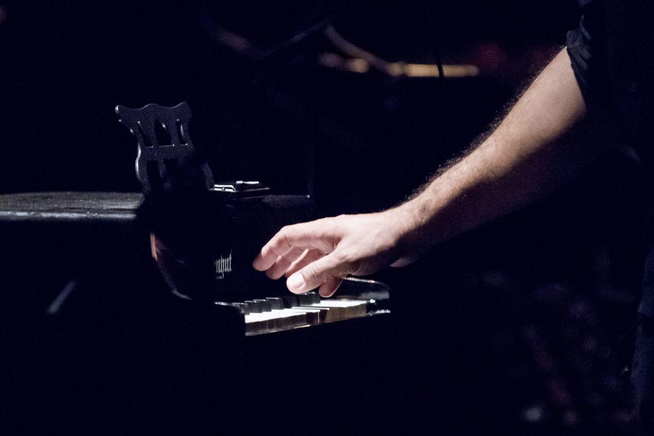 Ręka z podwiniętym do łokcia rękawem koszuli, z dłonią zawieszoną nad klawiaturą fortepianu.
