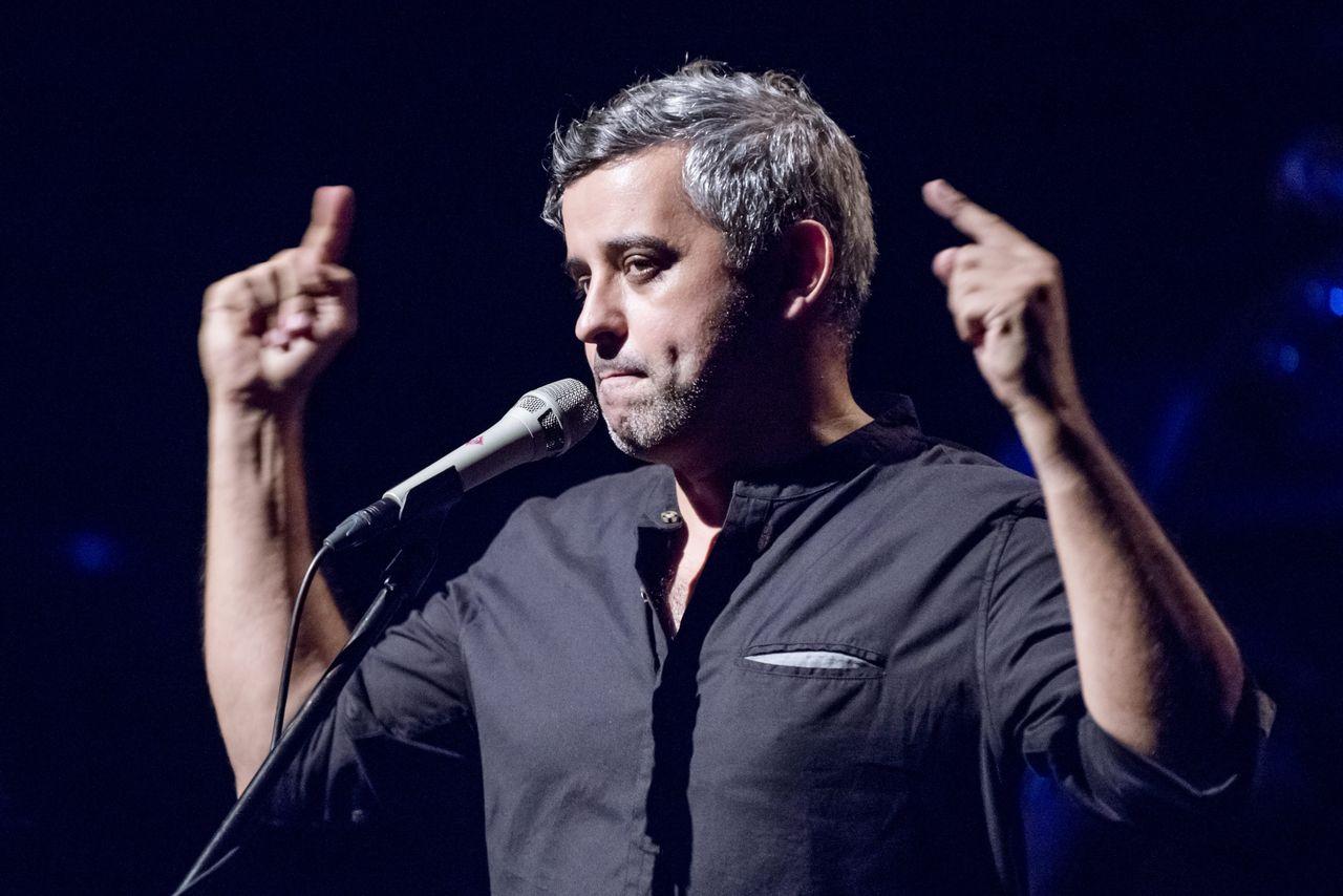 Konrad Imiela przed mikrofonem. Artysta ubrany jest w czarną koszulę, obie ręce z wyprostowanymi palcami wskazującymi wznosi na wysokość czoła.