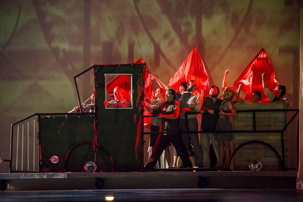 Metalowa makieta półciężarowego samochodu, z kierowcą i grupą ludzi z tyłu. Auto wygląda jak z czasów komunizmu, śpiewający ludzie ubrani w beżowe i szare stroje, mają w tle czerwone sztandary.