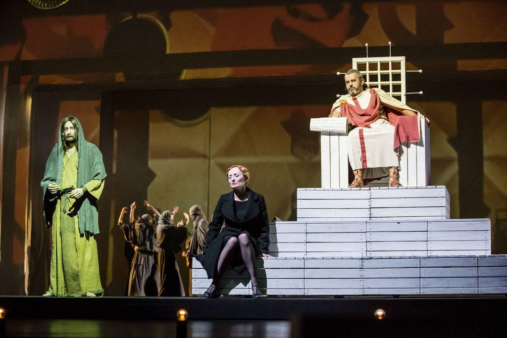 Z prawej, na białym, wysokim tronie siedzi Piłat w rzymskim, bogatym stroju. Na najniższym stopniu tronu, z lewej strony przysiadła Kobieta w czarnym płaszczu. Jest smutna, ma zamknięte oczy. Z lewej strony stoi długowłosy i zarośnięty Jeszua, w długiej, zniszczonej szacie, ma skute łańcuchem ręce. W głębi widać grupkę postaci w brązowych strojach z czasów Chrystusa.