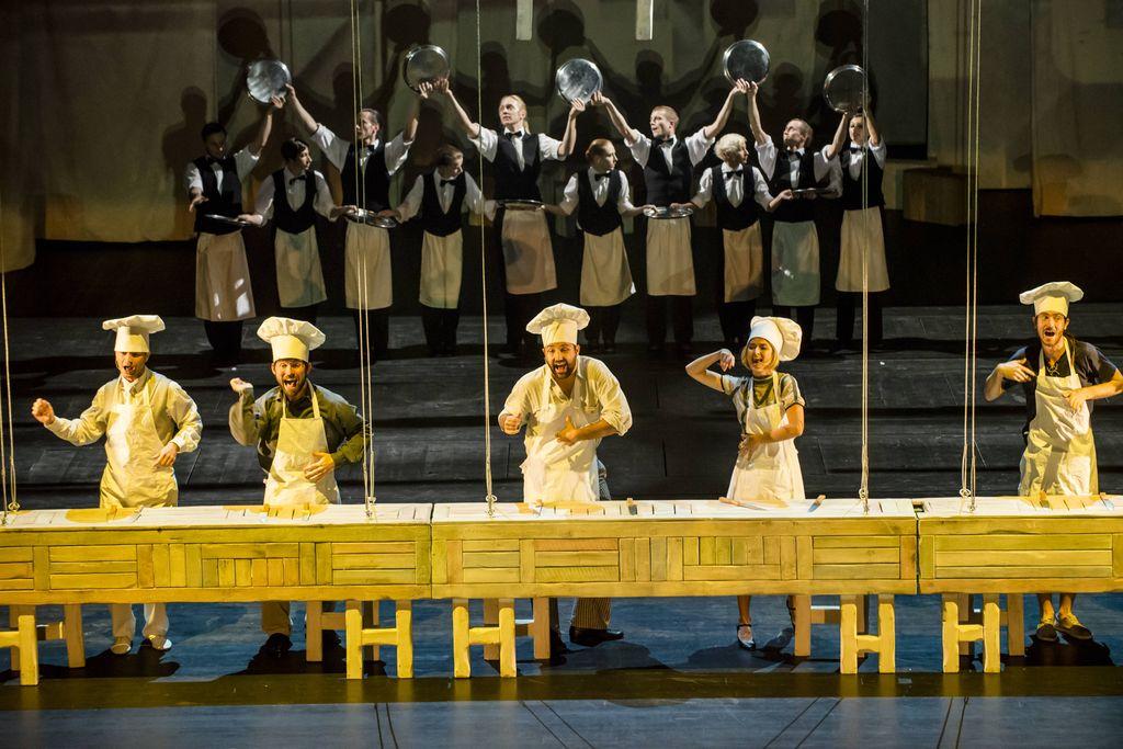 Na pierwszym planie długi drewniany stół, żółto oświetlony. Za nim znajduje się pięć śpiewających i gestykulujących osób, stoją w rzędzie, wzdłuż stołu. Czterech mężczyzn i jedna kobieta mają na sobie stroje kucharzy – fartuchy i charakterystyczne, wysokie czapki. W tle za nimi widać grupę tancerzy w strojach kelnerskich: ciemnych spodniach i kamizelkach, białych koszulach i zapaskach, z muszkami pod szyją. W rękach trzymają okrągłe tace.