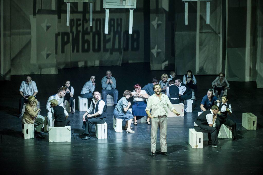 """Na scenie znajduje się ponad dwadzieścia osób – kobiet i mężczyzn. Mężczyzna na pierwszym planie stoi i śpiewa, inni siedzą na odwróconych, drewnianych skrzynkach. Ubrani są w codzienne stroje. U góry wiszą drewniane stoliki, w tle widoczna jest płachta tkaniny z rosyjskim napisem: """"Restauracja Gribojedow""""."""