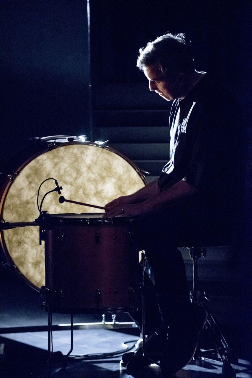 Scena w mroku, Piotr Dziubek gra na stojącym bębnie tom-tom. Obok niego stoi podświetlony od tyłu bęben wielki (gran cassa). Artysta widoczny jest z lewego profilu, pochyla się nad instrumentem, lewą rękę położył na membranie bębna, w prawej trzyma pałeczkę