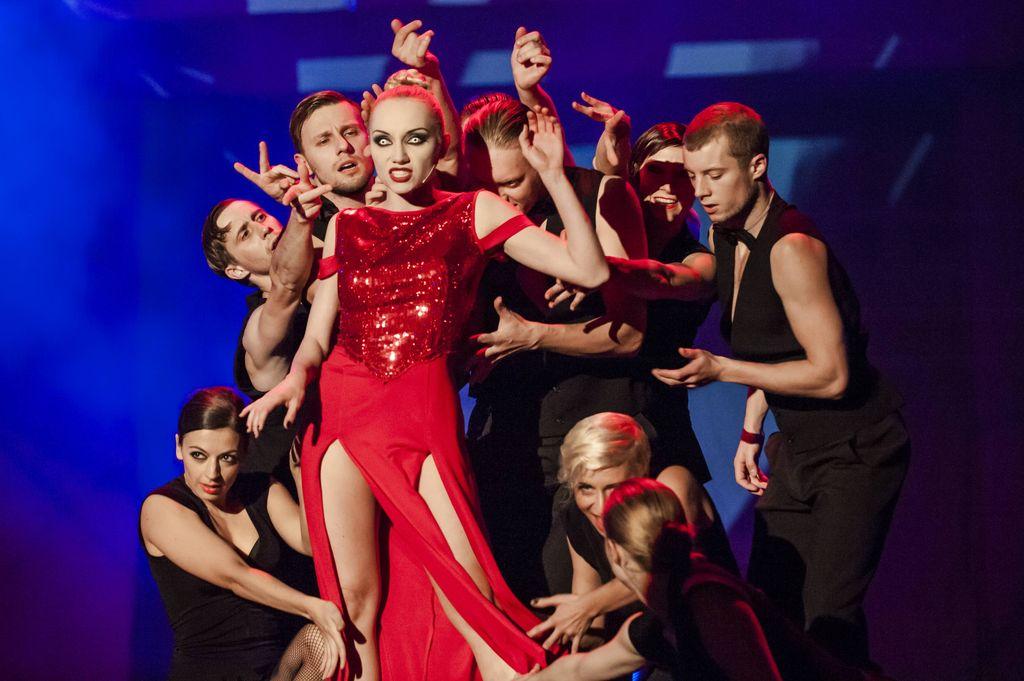 Hella w czerwonej, błyszczącej, wysoko rozciętej, długiej sukni, stoi na środku grupy otaczających ją tancerzy. Wygląda jakby coś mówiła, ma jasne splecione włosy, mocny makijaż i białe gałki oczne, bez tęczówek, jedynie z czarną źrenicą. Tancerze ubrani są w czarne kamizelki i spodnie, wyciągają ręce w kierunku Helli.