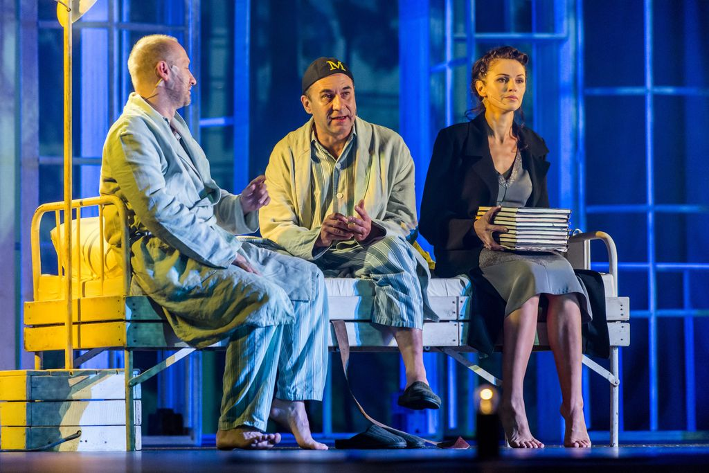 """Na szpitalnym, białym łóżku siedzą trzy osoby. Z lewej Iwan Bezdomny, obok niego Mistrz, a z prawej – Małgorzata. Rozmawiający mężczyźni są ubrani w pasiaste piżamy i jasne szlafroki, Mistrz ma na głowie czarną czapeczkę – myckę, z żółtą literą """"M"""". Małgorzata ma na sobie czarny płaszcz i szarą sukienkę, ciemne włosy są upięte. Na kolanach trzyma stertę dużych zeszytów, patrzy przed siebie."""