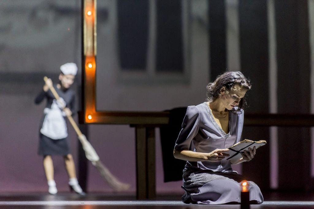 Z prawej strony siedząca kobieta, w jasnofioletowej sukience, pochyla głowę nad trzymanym w dłoniach plikiem kartek, przewiązanych wstążką. W tle, w nieostrości, widoczna duża rama obrazu, obok niej postać sprzątającej pokojówki, z miotłą w dłoniach.