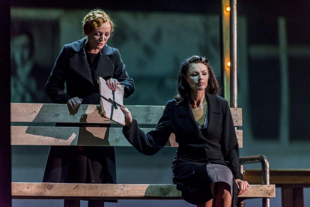 Na zdjęciu są dwie kobiety, ta z przodu siedzi na ławce, druga stoi z lewej strony, za oparciem ławki. Obydwie są ubrane w skromne, czarne płaszcze. Ciemnowłosa, siedząca Małgorzata prawą ręką trzyma w górze plik przewiązanych wstążką kartek, które jdnocześnie trzyma także rudowłosa Kobieta z rozmazanym makijażem oczu.