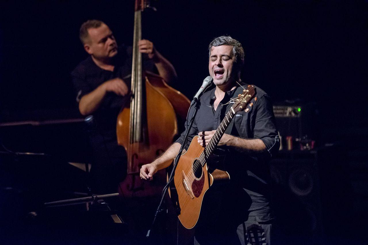 Adam Skrzypek z kontrabasem i Konrad Imiela z gitarą, śpiewający do mikrofonu na statywie.
