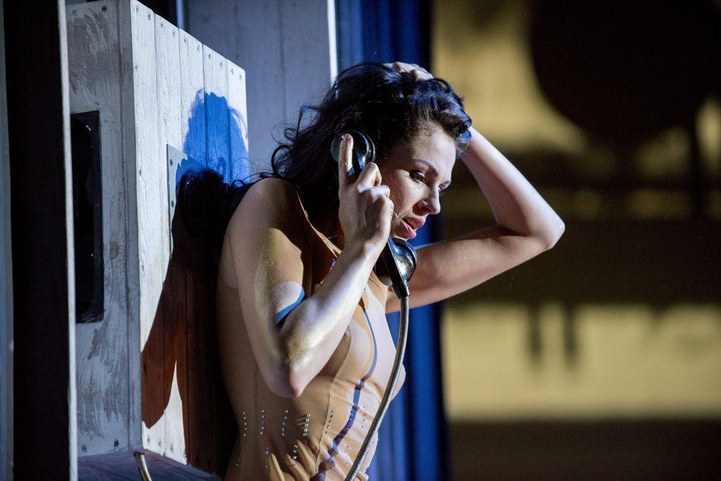 Małgorzata odwrócona plecami do drewnianej konstrukcji, która pełni rolę ścianki budki telefonicznej. W prawej ręce trzyma przyłożoną do ucha słuchawkę starego aparatu telefonicznego, mówi coś do niej. Drugą dłoń położyła na lekko pochylonej głowie. Ma rozpuszczone, ciemne, lekko kręcone włosy, ubrana jest w skąpą, cielistą sukienkę.