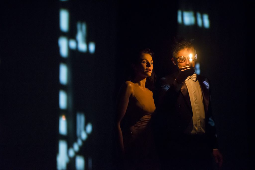 Ciemny kadr, oświetlony płomieniem świecy. W jej świetle widoczne są dwie postaci. Z lewej stoi Małgorzata, z rozpuszczonymi włosami, w cielistym stroju, patrzy w stronę świecy trzymanej w prawej dłoni przez Korowiowa. Mężczyzna ubrany jest w ciemny frak, ma białą koszulę i muszkę, nosi okulary z okrągłą oprawką szkieł.
