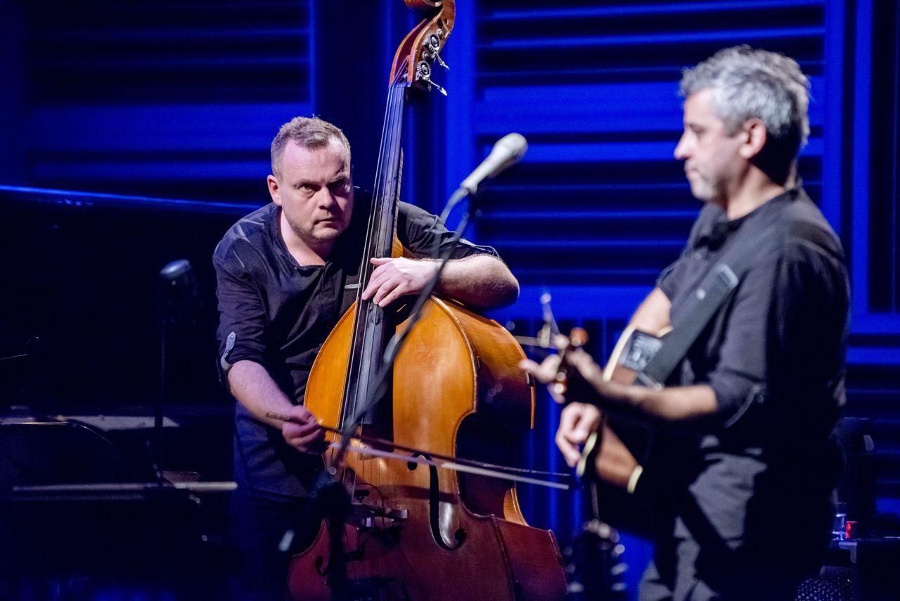 Adam Skrzypek przy kontrabasie i Konrad Imiela z gitarą. Tło sceny oświetlone na niebiesko, artyści ubrani w czarne koszule i spodnie.