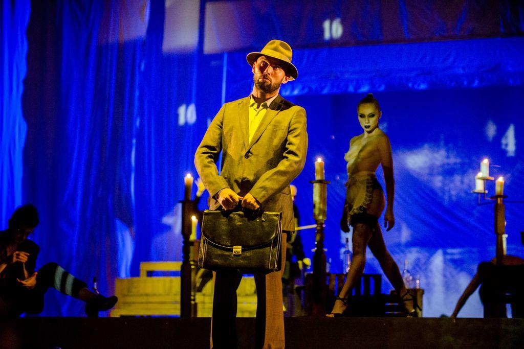 Na pierwszym planie, oświetlony żółtym światłem, stoi mężczyzna ubrany w garnitur, trzyma w rękach sfatygowaną, staroświecką teczkę. Fokicz ma na lekko uniesionej głowie kapelusz, spogląda w górę. Za nim, na niebieskim tle widoczna, jest półnaga, mocno umalowana Hella. Wygląda jakby szła w kierunku Fokicza, patrzy w jego stronę.