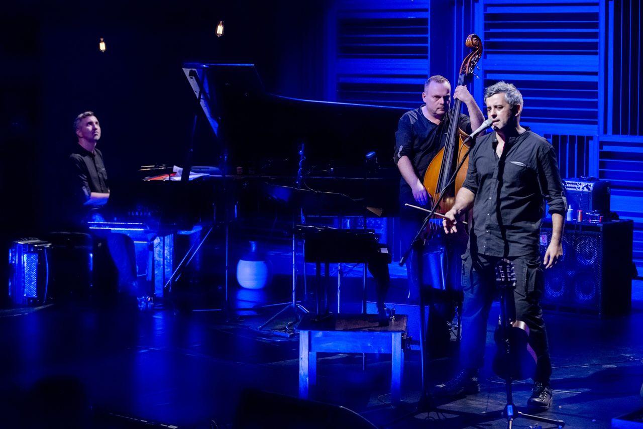 Piotr Dziubek przy fortepianie, Adam Skrzypek z kontrabasem i Konrad Imiela przy mikrofonie na scenie oświetlonej niebieskim światłem. Artyści ubrani są w czarne koszule i spodnie.