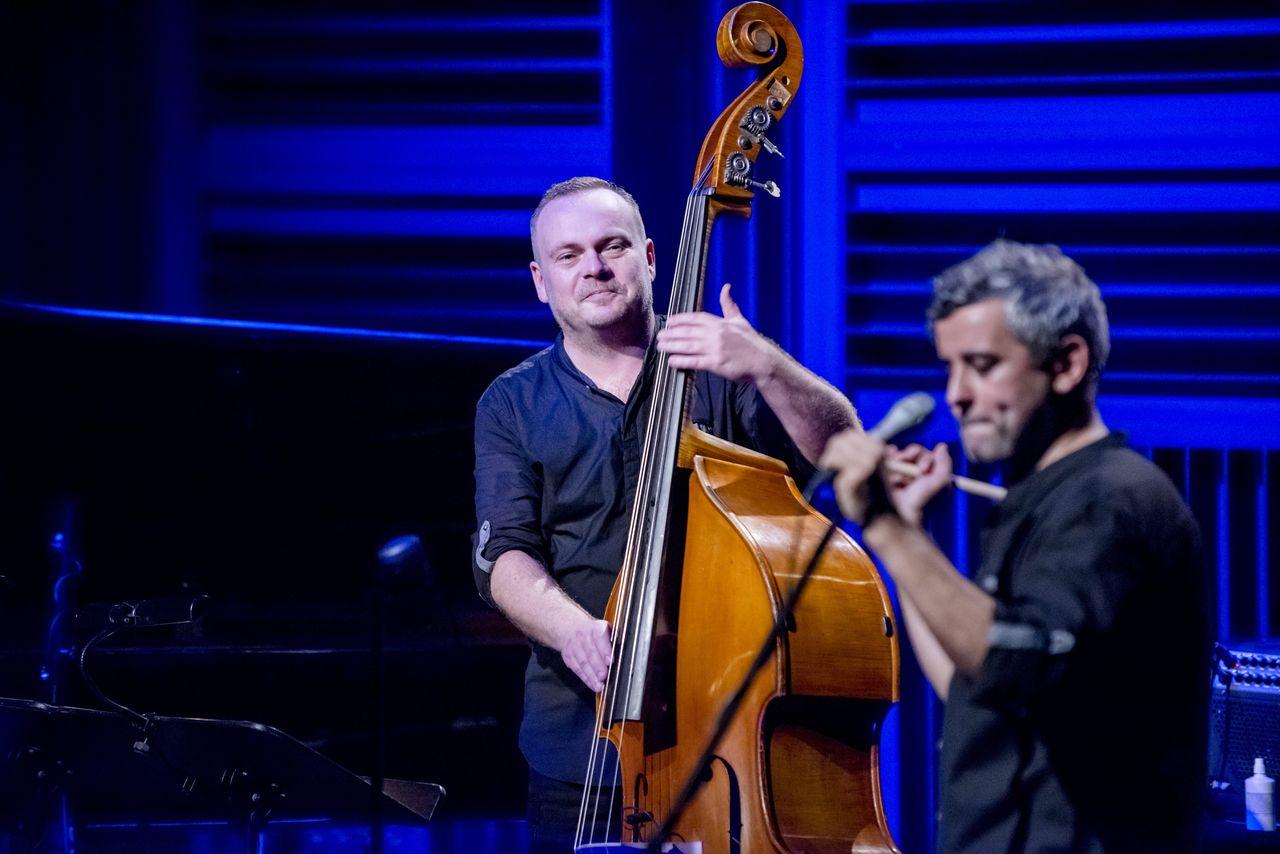 Tło sceny oświetlone na niebiesko. W centrum kadru Adam Skrzypek gra na kontrabasie, po lewej Konrad Imiela przed mikrofonem. Artyści ubrani są w czarne koszule z podwiniętymi rękawami i czarne spodnie.