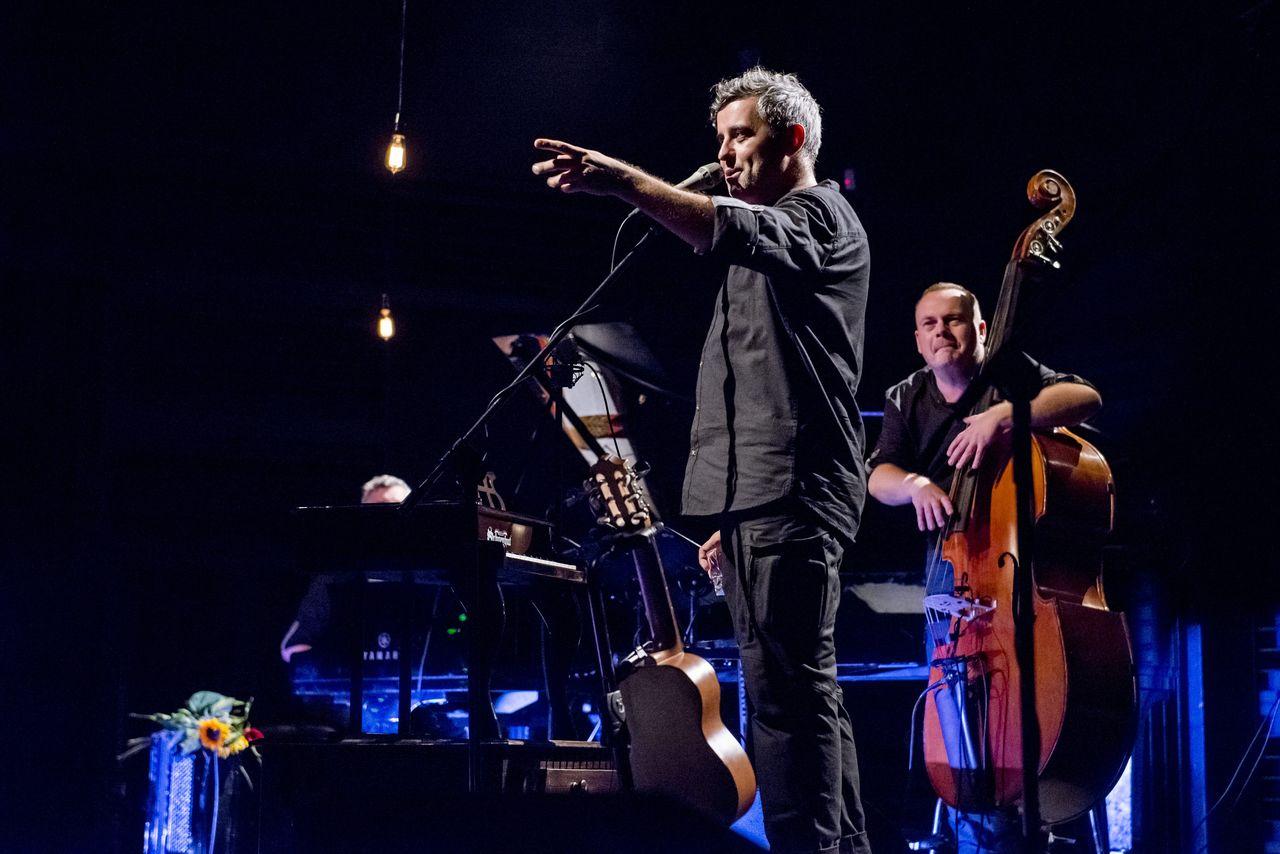 Przed mikrofonem stoi Konrad Imiela, zwrócony do widza lewym półprofilem. Wyciągniętą lewą ręką wskazuje w stronę widowni. Za nim w tle nieostra postać Adama Sktzypka przy kontrabasie i stojąca na podłodze gitara.