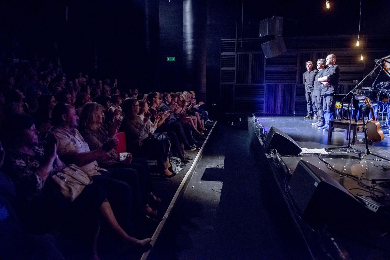 Ujęcie z boku widowni, po lewej stronie klaszcząca publiczność, po prawej stojący na scenie artyści: Piotr Dziubek, Adam Skrzypek i Konrad Imiela, ubrani w czarne koszule i spodnie.
