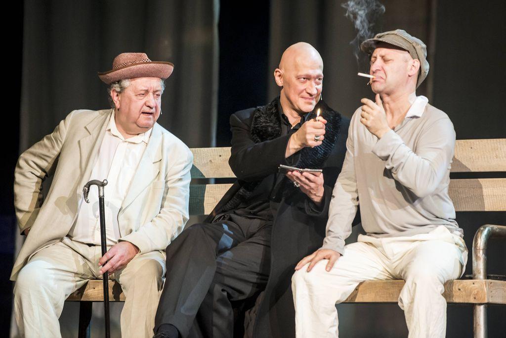 Trzej mężczyźni siedzą na drewnianej ławce. Pośrodku Woland w czarnym płaszczu, skierowany w prawo, ku Iwanowi Bezdomnemu. Iwan ma w ustach zapalonego papierosa, Woland trzyma w prawej ręce zapaloną zapalniczkę, a w lewej – srebrną papierośnicę. Przygląda się im siedzący z lewej Berlioz, w jasnym garniturze i jasnej koszuli, w słomkowym kapeluszu, trzymający w lewej dłoni czarną laskę ze srebrnym uchwytem.