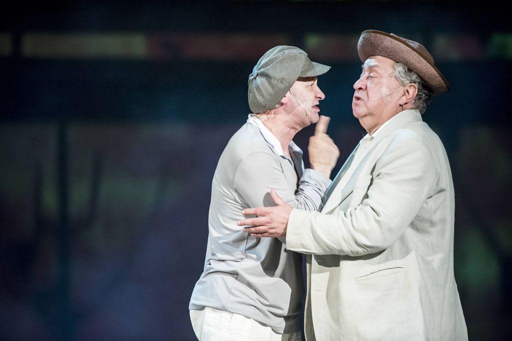 Dwaj mężczyźni skierowani twarzą do siebie, jeden tuż przy drugim. Obydwaj w jasnych ubraniach. Iwan Bezdomny, w kaszkiecie na głowie, mówi coś do Berlioza, energicznie potrząsając uniesioną dłonią z wyciągniętym wskazującym palcem. Berlioz, w kapeluszu z wywiniętym w górę rondem, także coś mówi, patrząc w stronę Bezdomnego.