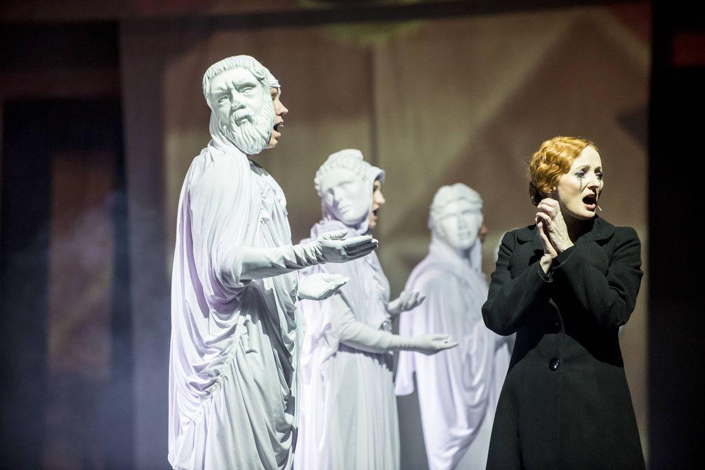 Z lewej strony stoją w rzędzie trzy postaci w białych, udrapowanych szatach i maskach, stylizowane na rzymskie posągi. Po prawej znajduje się rudowłosa Kobieta w czarnym płaszczu, ma bladą twarz i rozmazany makijaż oczu. Wszyscy mają otwarte usta, wyglądają jakby śpiewali.