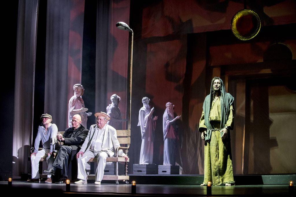 Z lewej strony, na ławeczce stojącej przy latarni, siedzą trzej mężczyźni: Iwan Bezdomny w jasnej bluzie, spodniach i kaszkiecie, pośrodku – Woland, cały w czerni, opierający dłonie na lasce, z prawej – Berlioz, w jasnej koszuli, marynarce i spodniach, w słomkowym kapeluszu. Za nimi, na podestach ze skrzynek, stoją cztery postaci stylizowane na dawne posągi. Z prawej strony stoi wysoki mężczyzna w zniszczonej, długiej szacie. Ma długie włosy, brodę i wąsy, głowę zakrytą kapturem.