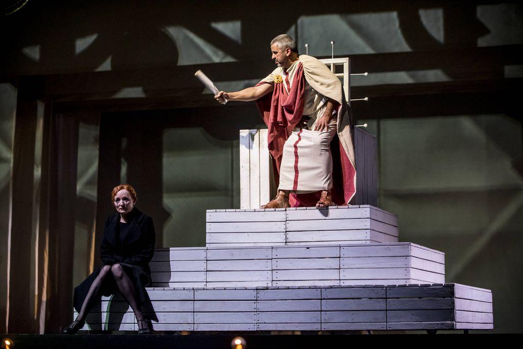 Na drewnianym, wysokim tronie, siedzi mężczyzna w bogatym, rzymskim stroju. Piłat wyciąga prawą dłoń z papierem zwiniętym w rulon, w kierunku kobiety w czerni, która siedzi na najniższym podeście tronu. Kobieta ma smutną, bladą twarz, z rozmazanym makijażem oczu.