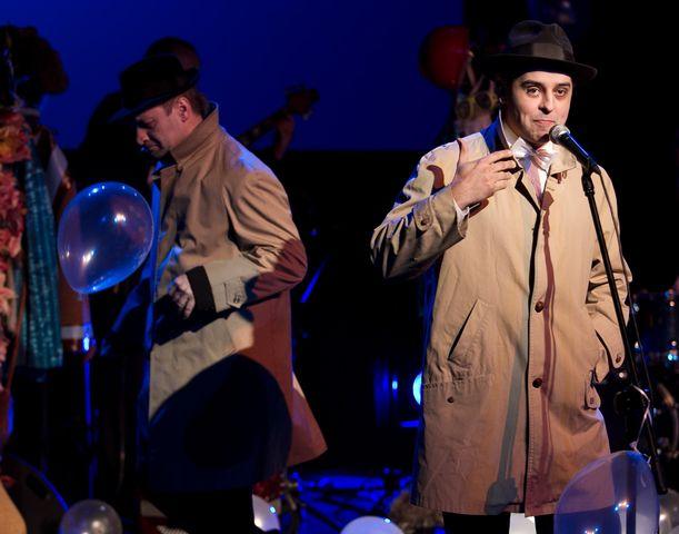 Przy mikrofonie stoi mężczyzna w jasnym, długim płaszczu w typie prochowca, na głowie ma ciemny, klasyczny kapelusz. Mówi lub śpiewa do mikrofonu, w tle widać przechodzącego drugiego artystę, ubranego także w płaszcz i kapelusz. Do mikrofonu przyczepiony jest przezroczysty balon.