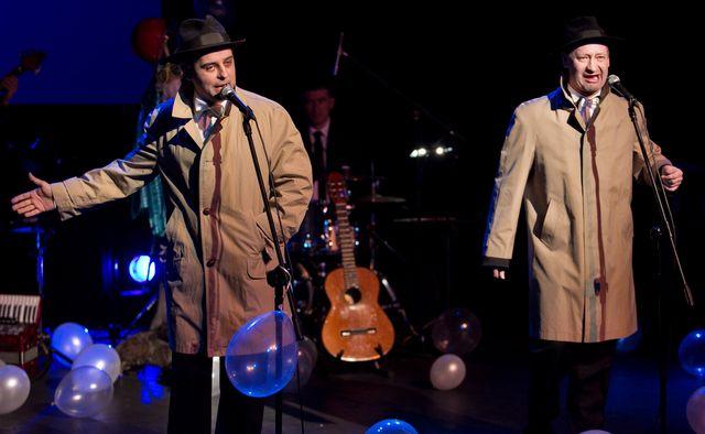 Dwaj mężczyźni śpiewają do stojących mikrofonów. Artyści ubrani są w długie, jasne płaszcze, w typie prochowca, na głowach mają klasyczne, ciemne kapelusze. W tle widać instrumenty, muzyków, porozrzucane, jasne balony.