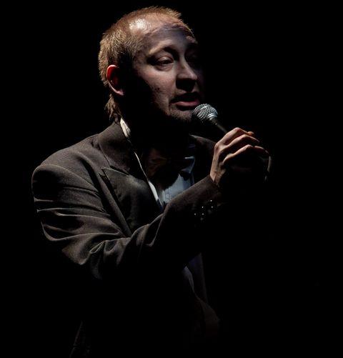 Ciemne tło, z ciemności wyłania się widoczna od pasa w górę sylwetka śpiewającego artysty. Mężczyzna ubrany jest w ciemną marynarkę, białą koszulę z muszką, w prawej dłoni trzyma mikrofon.