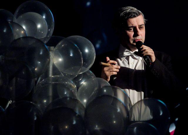 Ciemnowłosy mężczyzna w czarnym fraku i białej koszuli z muszką, śpiewa, trzymając w lewej dłoni mikrofon. W prawej , uniesionej dłoni ma zapalone cygaro. Większą część kadru, od lewej strony, zajmuje sterta nadmuchanych, przezroczystych balonów.