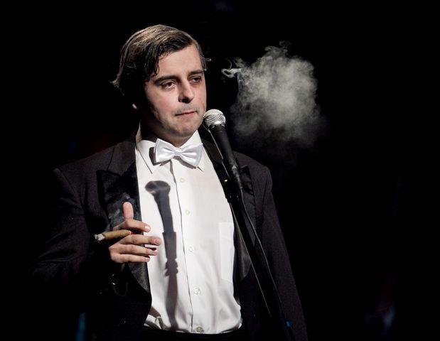 Ciemnowłosy mężczyzna w czarnym fraku, białej koszuli z muszką, stoi przy mikrofonie. W prawej , uniesionej dłoni trzyma zapalone cygaro, na wysokości jego głowy znajduje się obłoczek dymu z cygara.