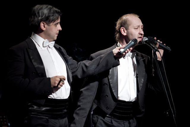 Dwaj mężczyźni, jeden z ciemnymi, siwiejącymi włosami, drugi - łysiejący blondyn, stoją obok siebie. Ten z lewej wyciąga w kierunku drugiego mikrofon, w prawej dłoni ma zapalone cygaro. Artysta z prawej mówi lub śpiewa do stojącego mikrofonu, trzymając w lewej dłoni jeszcze jeden mikrofon. Artyści ubrani są jednakowo – w czarne fraki i spodnie, białe koszule z białymi muszkami, pasy smokingowe.