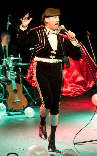 Mężczyzna w stroju torreadora, z krótką, podbitą czerwonym atłasem peleryną, w tanecznej pozie. W lewej dłoni trzyma mikrofon, do którego śpiewa, prawą dłoń ma uniesioną na wysokości głowy. Strój dopełniają groteskowe skarpety podciągnięte na gołych łydkach i ciemne buty. W tle widać opartą o stojak gitarę i perkusistę.