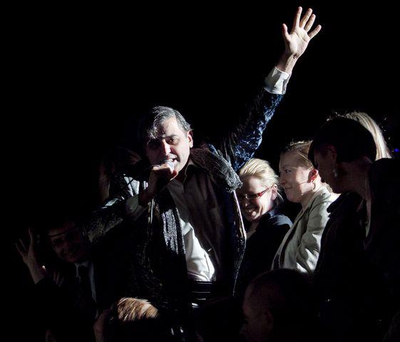 Ciemnowłosy, śpiewający mężczyzna z mikrofonem w prawej dłoni, z lewą ręką uniesioną ku górze, znajduje się na widowni, wśród publiczności. Kobiety, przy których przysiadł, patrzą na niego z uśmiechem.