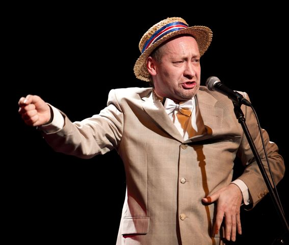 Mężczyzna w jasnym, słomkowym kapeluszu mówi lub śpiewa do mikrofonu. Ma na sobie jasną marynarkę i koszulę z muszką. Prawą, zaciśniętą w pięść dłoń, kieruje w bok, drugą, z rozłożonymi palcami, trzyma na wysokości lewej kieszeni marynarki.