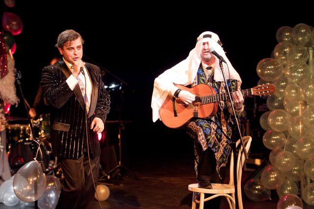 Dwaj śpiewający mężczyźni, jeden w prawej dłoni trzyma mikrofon, drugi – stoi z gitarą przed mikrofonem, opierając prawą nogę na siedzeniu krzesła. Artysta z lewej ubrany jest w ciemną marynarkę z błyszczącymi prążkami i ciemne spodnie, ten z prawej ma na sobie długą, kolorową szatę, a na głowie białą chustę, charakterystyczną dla stroju szejków arabskich. W tle widać dużo balonów i elementy garderoby.
