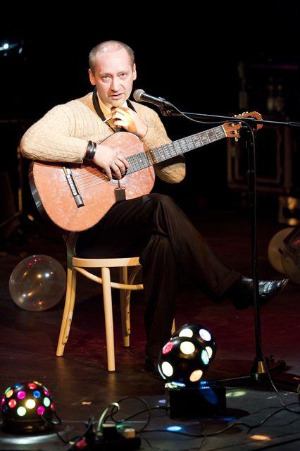 Łysiejący blondyn siedzi na krześle, nogę ma założoną na nogę. Trzyma gitarę, mówi coś lub śpiewa do mikrofonu. Ma na sobie jasny, dzianinowy sweter i ciemne spodnie. Przed nim znajdują się świecące kule.