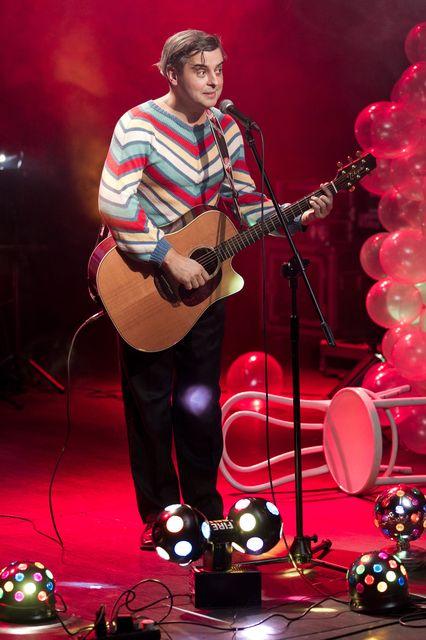 Ciemnowłosy mężczyzna stoi przy mikrofonie, mówi do niego lub śpiewa. Ubrany jest w kolorowy, pasiasty sweterek i ciemne spodnie, trzyma gitarę. Tło jest podświetlone na czerwono, z prawej strony leży przewrócone, białe krzesło, widać też dużo balonów. Przed artystą znajdują się świecące kule.