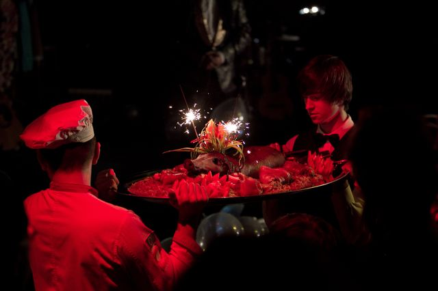 Dwaj mężczyźni wnoszą na dużej tacy udekorowanego zapalonymi, sztucznymi ogniami, upieczonego prosiaka. Tło jest ciemne, mężczyźni podświetleni czerwonym światłem.