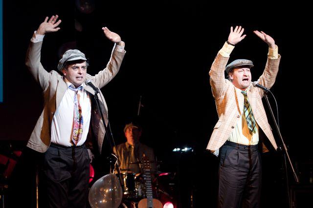 Dwaj śpiewający mężczyźni stoją przy mikrofonach. Ubrani są jednakowo, w jasne marynarki, ciemne spodnie, białe koszule, kolorowe krawaty, czapki – kaszkiety. Mają obydwaj ręce rozłożone i wyciągnięte do góry. W tle widać perkusistę.