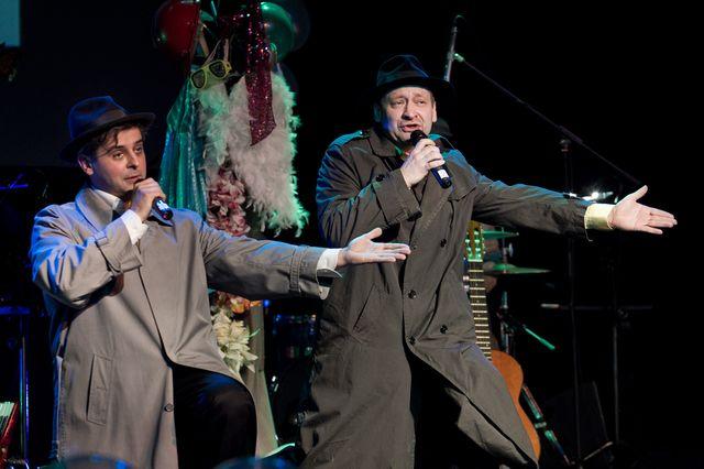 Dwaj mężczyźni śpiewający do mikrofonów, trzymanych w prawych dłoniach, lewe dłonie wyciągnięte są w bok. Artyści ubrani są w długie płaszcze, w typie prochowca, jeden jest ciemny, drugi jasny. Na głowach mają klasyczne kapelusze. W tle widać instrumenty i elementy garderoby.