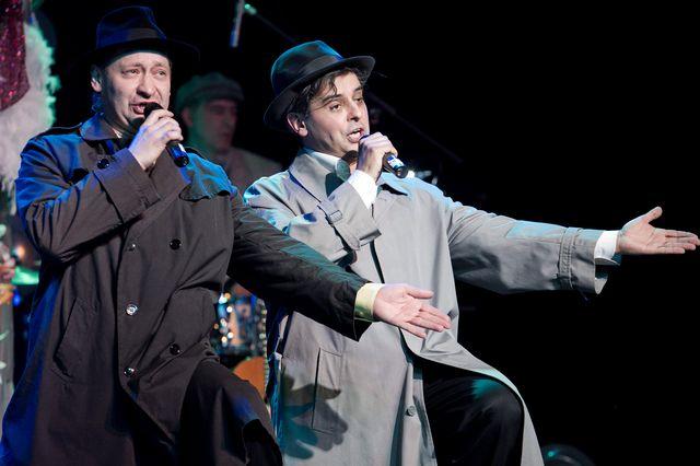 Dwaj mężczyźni śpiewający do mikrofonów, trzymanych w prawych dłoniach, lewe dłonie wyciągnięte są w bok. Artyści ubrani są w długie płaszcze, w typie prochowca, jeden jest ciemny, drugi jasny. Na głowach mają klasyczne kapelusze. W tle widać perkusistę.