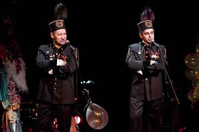 Dwaj śpiewający mężczyźni stoją przy mikrofonach. Ubrani są w galowe stroje górnicze, łącznie z charakterystycznymi nakryciami głowy. W ciemnym tle majaczą kolorowe balony, instrumenty i elementy garderoby.